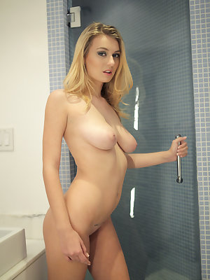 Natalia Star is ready to unwind after a long day, so she prepares for a long, steamy shower. As the water heats up, the slender blonde goddess inspects herself in the mirror and then lets the towel that covered her plentiful assets drop so that she can se