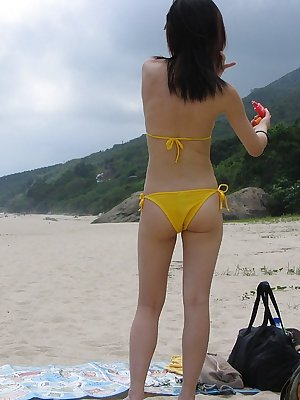 Pretty asian girl in wet bikini on the beach