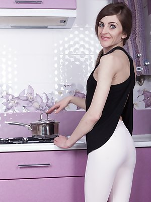 In her kitchen, Olivia Arden is horny. She takes off her black top and pink tights and climbs on the counter. She runs the faucet against her hairy pussy and is turned on. She opens her legs and show us.