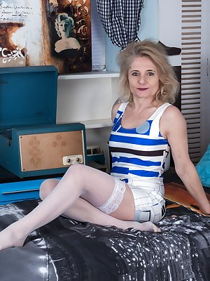 Isabella Diana is relaxing in her bedroom in her blue shirt and stockings. She strips naked and has a very hairy pussy. This 47 year-old beauty is all natural with B cup breasts and looks great.