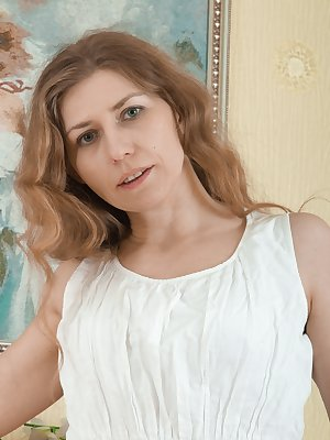 Elza is in her white dress and knee-high stockings. She has hairy pits and is eager to strip naked. She gets naked and lays on the wooden floor with legs open. Her hairy bush is flowing and she is sexy.