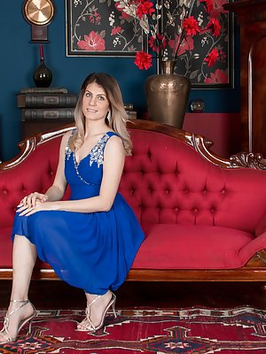 Ashleigh McKenzie is wearing her beautiful blue dress along side her red sofa. She strips it off and lays naked across the sofa. Her 32C breasts and hairy pussy show off her natural sexy body there.