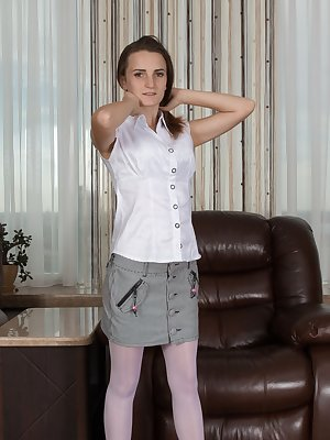 Ira is standing by her leather armchair, in her white blouse, grey skirt and stockings. She strips to just her stockings, and opens her legs wide to show her hairy pussy, plus shows her 32C breasts.