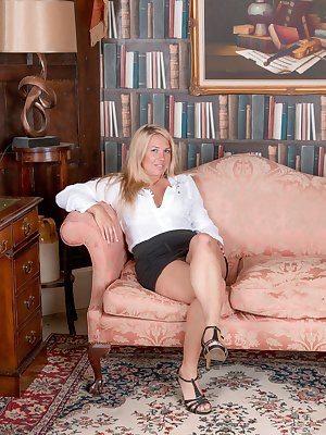 "Elle MacQueen lays across her sofa while in her study. She strips naked while relaxing, and shows off her blonde body and 5'5"" all-natural figure. Take a close look at her hairy bush for a treat."