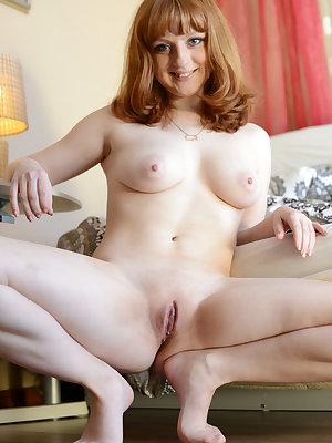 Redhead Kataly bares her luscious body as she poses on the sofa.