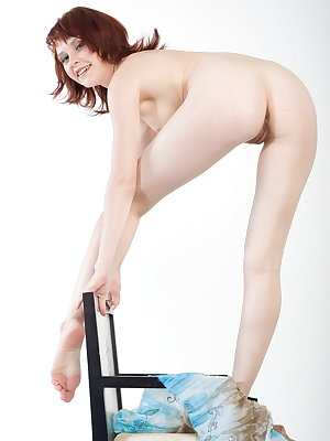 Redhead Anelie A bares her creamy white body and hairy pussy as she poses on the chair.
