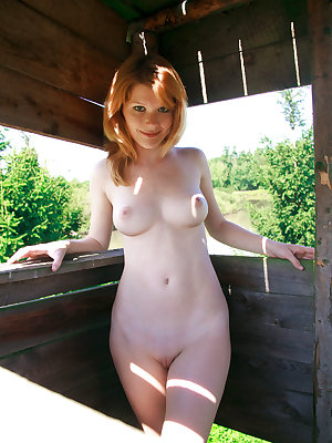 A pretty redhead debutante, with smooth, fair complexion, charming smile, and great body poses against the lush and verdant outdoor.