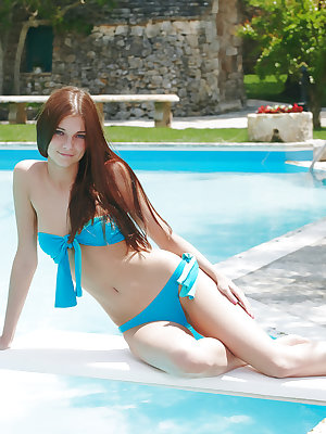 Belle confidently poses by the poolside, flaunting her breathtaking slender physique with magnificent puffy breasts, shaven pussy, tight butt, and a pair of long, svelte legs.