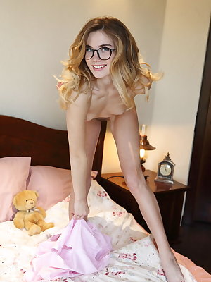 Lola Krit strips on the bed baring her small tits and trimmed pussy.
