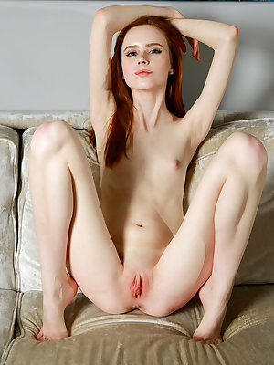 Redhead Bella Milano bares her creamy, petite body and pink pussy on the couch.