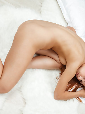 Horny redhead Carinela lays naked on the bed, stroking and fucking and pink pussy with her fingers