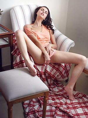 With explicit poses and beguiling, brown eyes, Nasita lays on the chair, stroking her sensitive clit