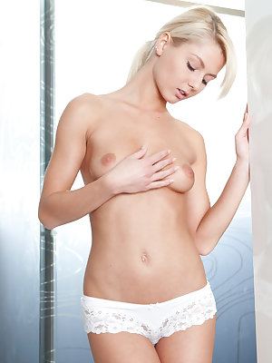 Wearing sexy white cheeky panties and a white tank top,   Grace C displays the look of an innocent blond nubile.