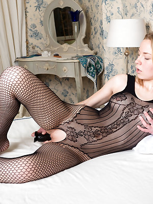 Emma O plays with her pussy as she inserts her black dildo.