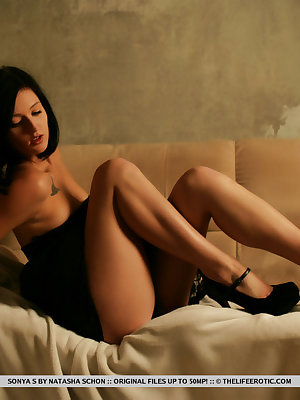 Sonya S erotically poses on the sofa as she pours hot candle wax on her body.