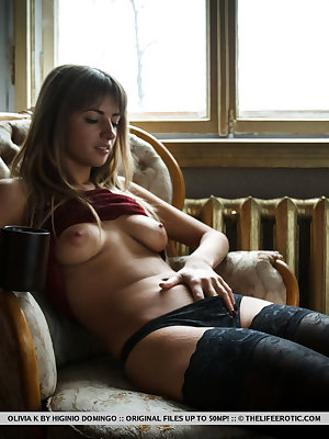 Olivia K cozy herself indoors with a cup of coffee before proceeding to finger fuck herself.