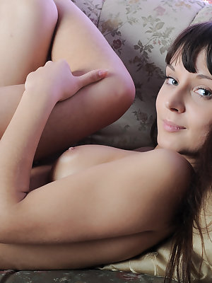 Gorgeous brunette posing in Eves costume on a simple sofa showing glowing beauty of her astonishing fresh body. Sexy nude shots.