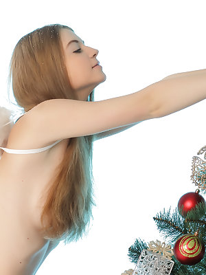 Beautiful long haired teen angel in white stockings showing her body near Christmas tree.