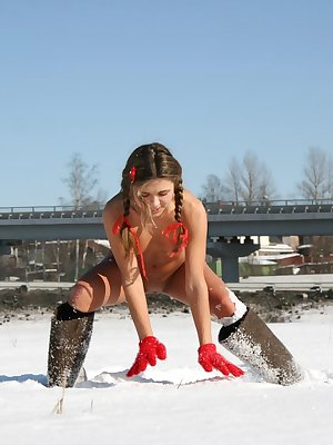 The incredible teen is standing in the white cold snow only in felt boots and plays with snowflakes.