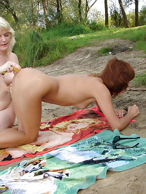 A couple of lesbians with super perky tits finger each other while laying on the beach